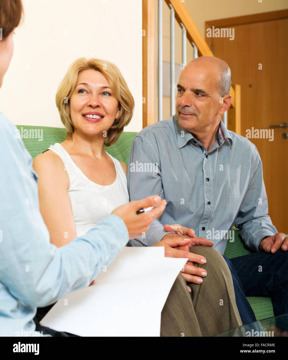 Happy mature couple discussing details of private