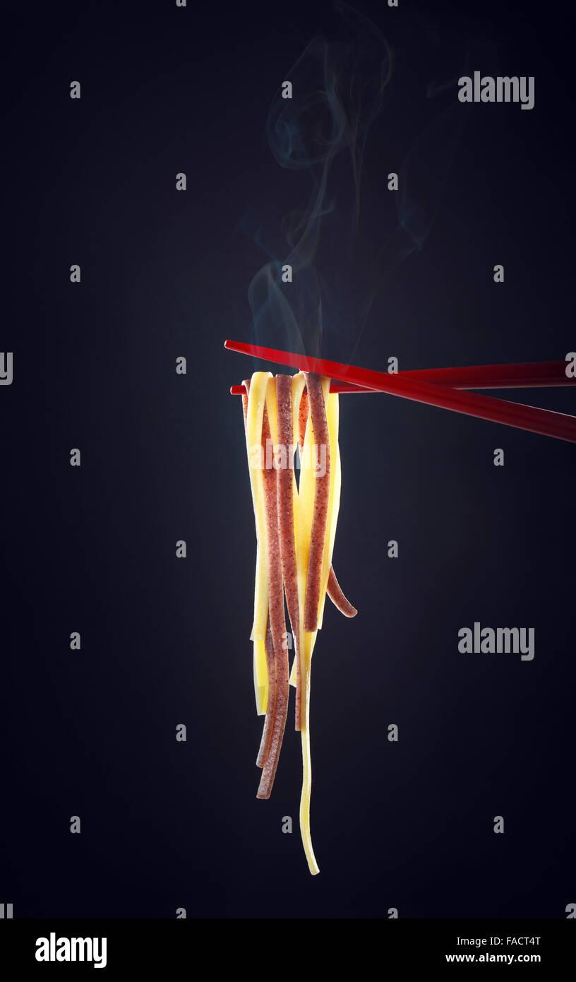 Steamy Noodles on Chopsticks - Stock Image