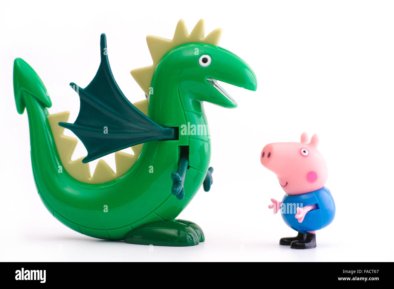 Tambov, Russian Federation - December 16, 2015 George Pig  toy character with green dinosaur on white background. - Stock Image