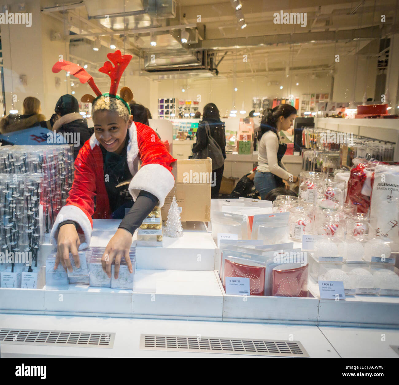 A worker dressed as a reindeer adjusts stock in the window of a store in New York on Wednesday, December 23, 2015. - Stock Image