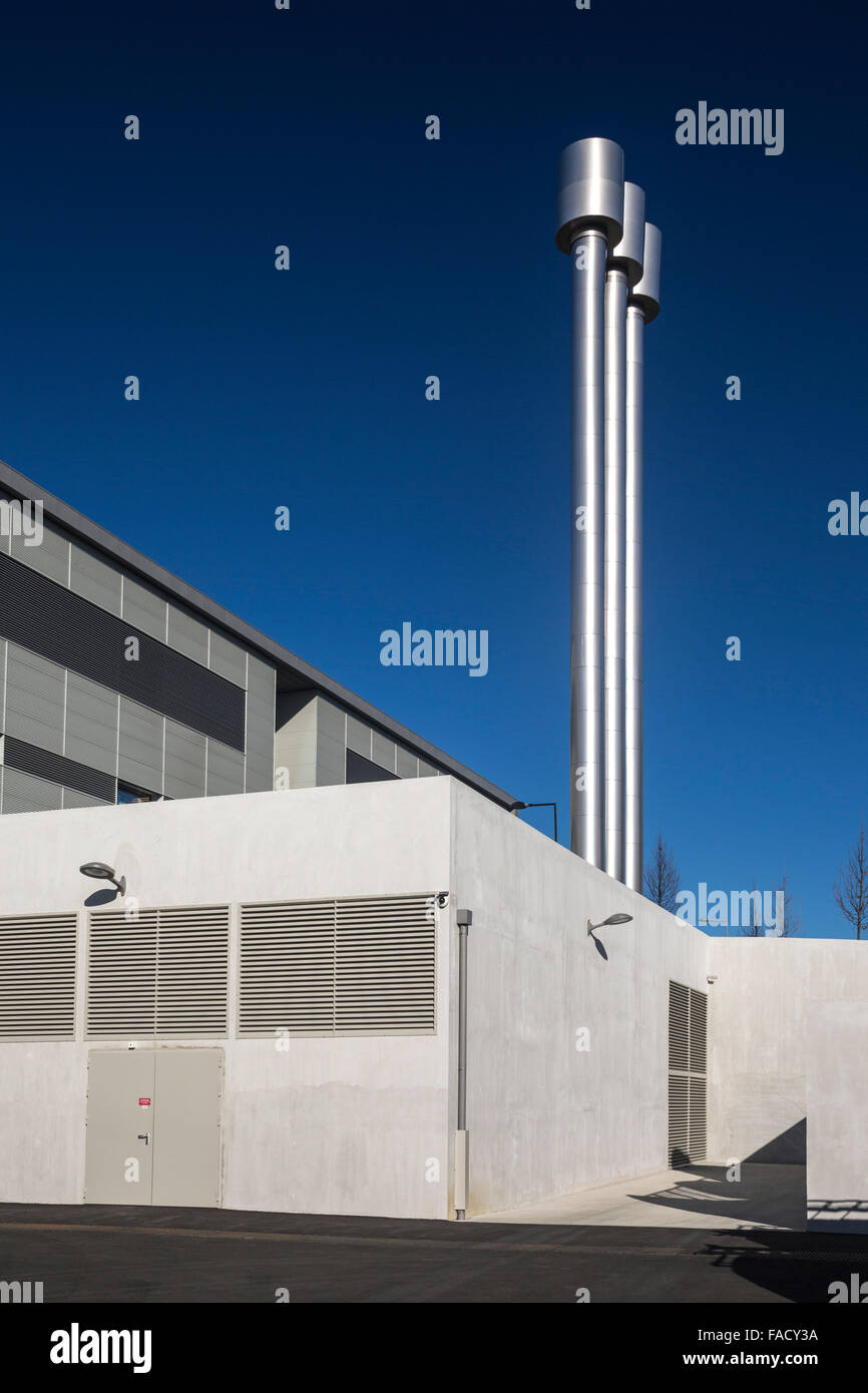 a modern industrial building with three metal chimneys (france stock