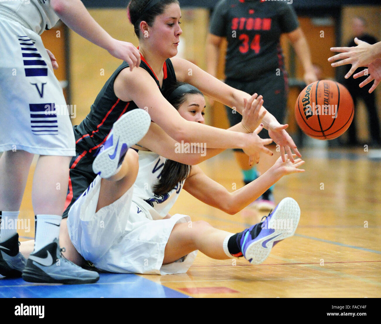 Players battle for possession of loose ball during a high school basketball game.USA. - Stock Image