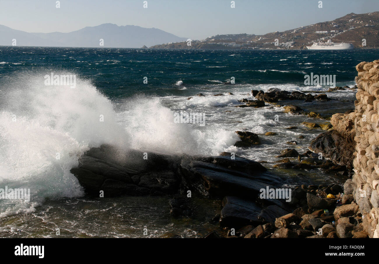 The waves breaking on a stony beach, forming a spray - Stock Image