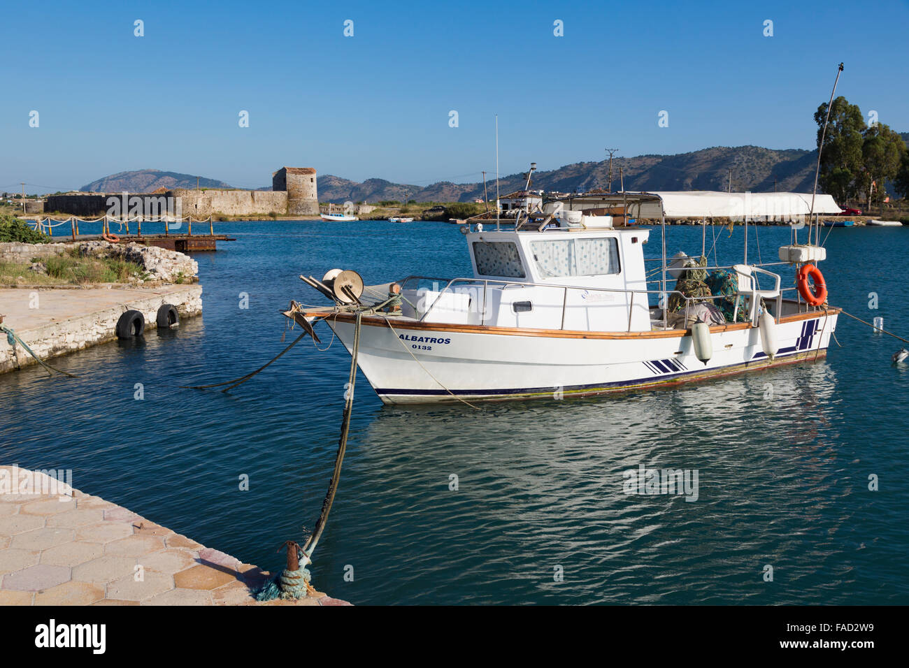 Butrint, Albania.  Fishing boat moored in the Vivari Channel front of the archaeological site. - Stock Image