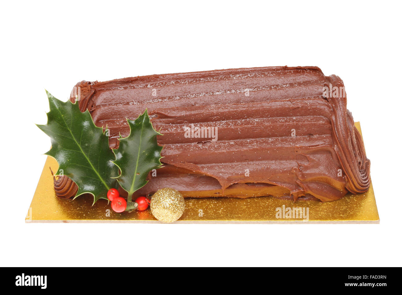Chocolate Yule log decorated with holly and a Christmas bauble isolated against white - Stock Image