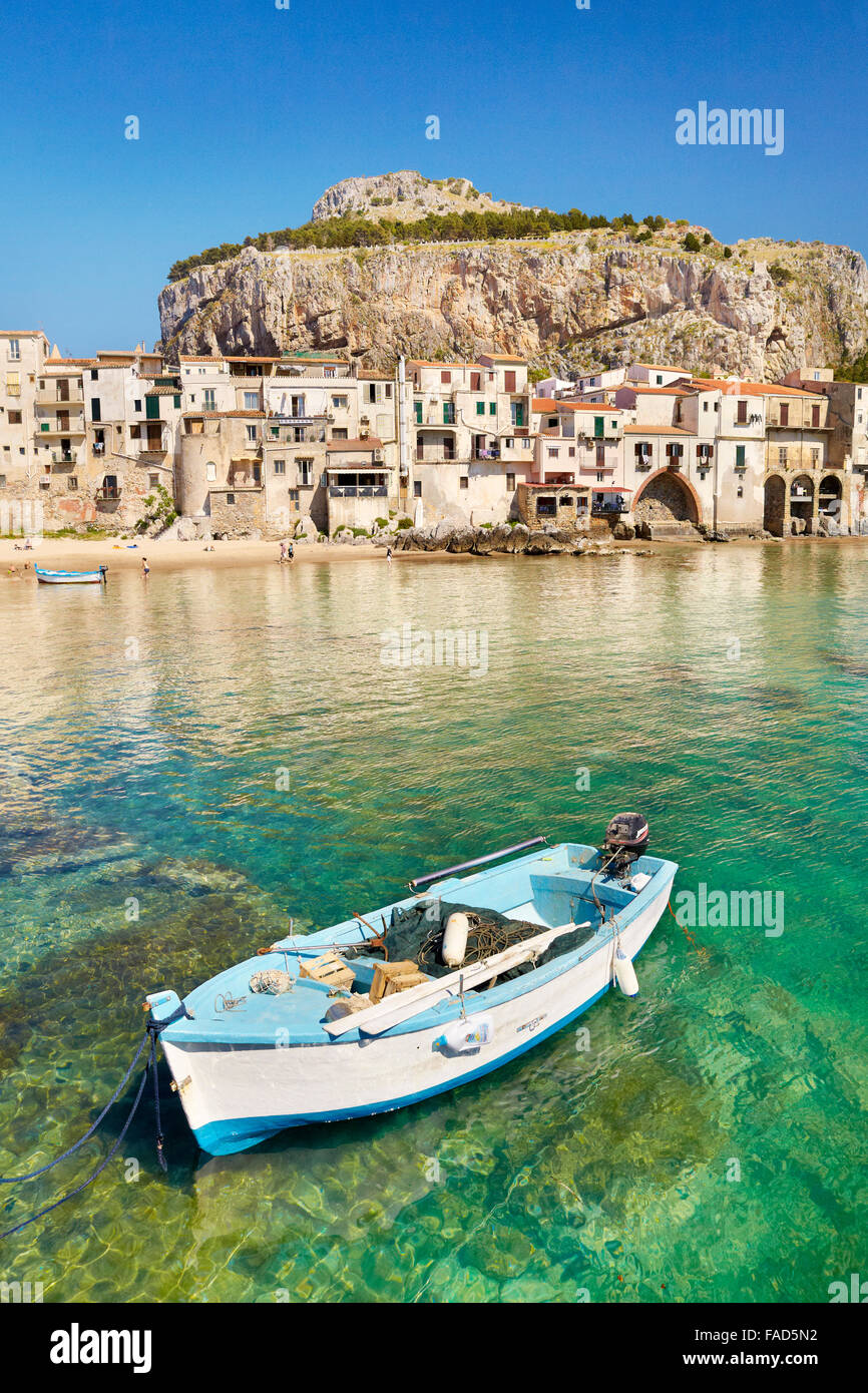 Fishing boat and medieval houses of Cefalu old town, Sicily, Italy - Stock Image