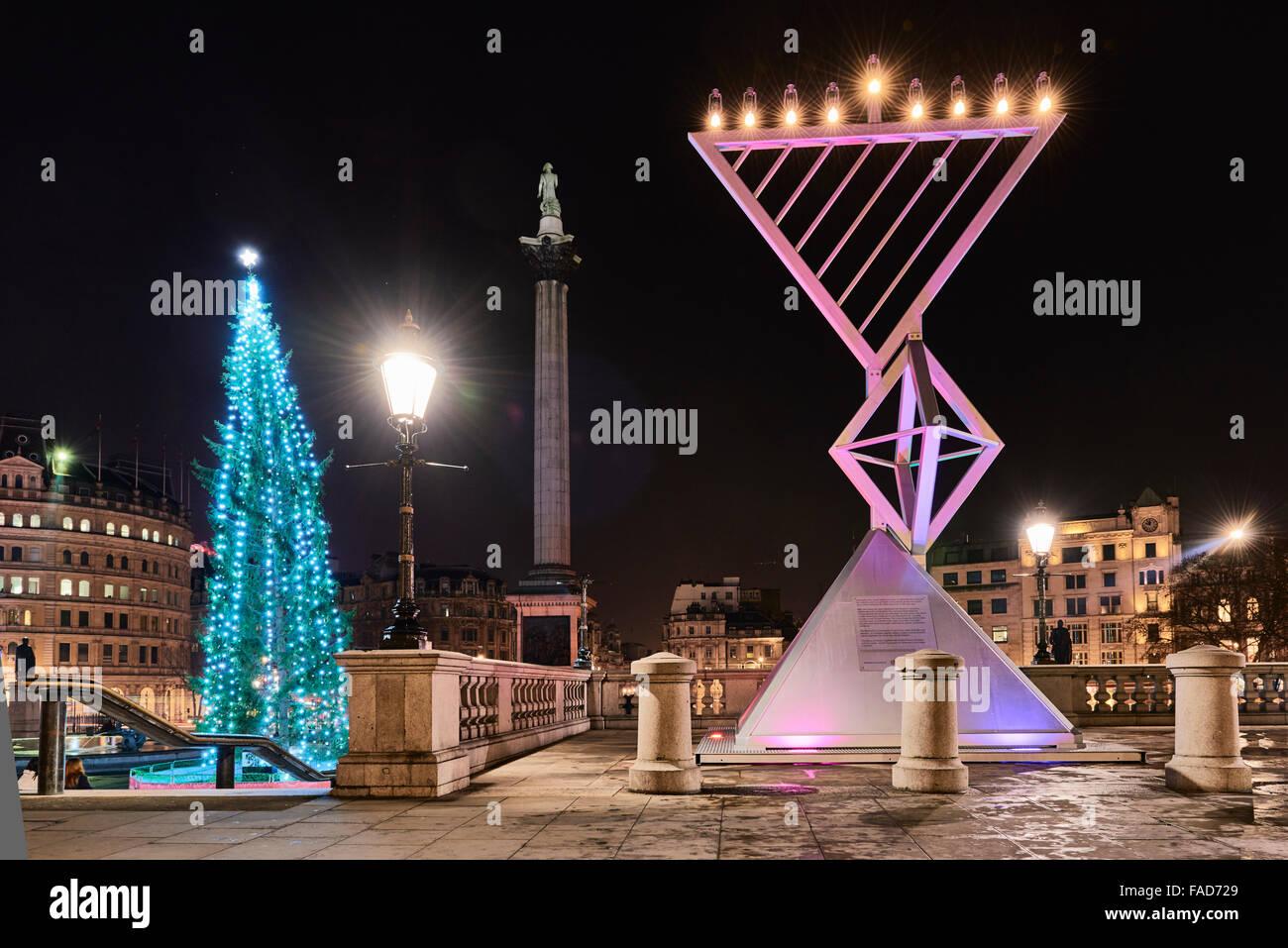 LONDON, UK - DECEMBER 19: Night shot of Menorah next to Christmas tree in Trafalgar Square, set up for Chanukah. - Stock Image