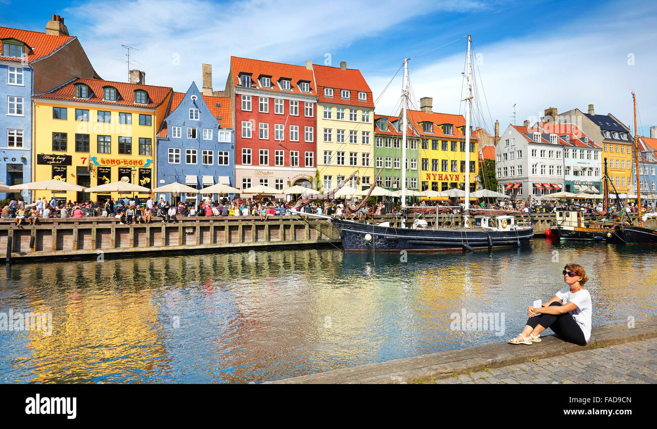 Copenhagen, Denmark - woman relaxing at Nyhavn Canal - Stock Image