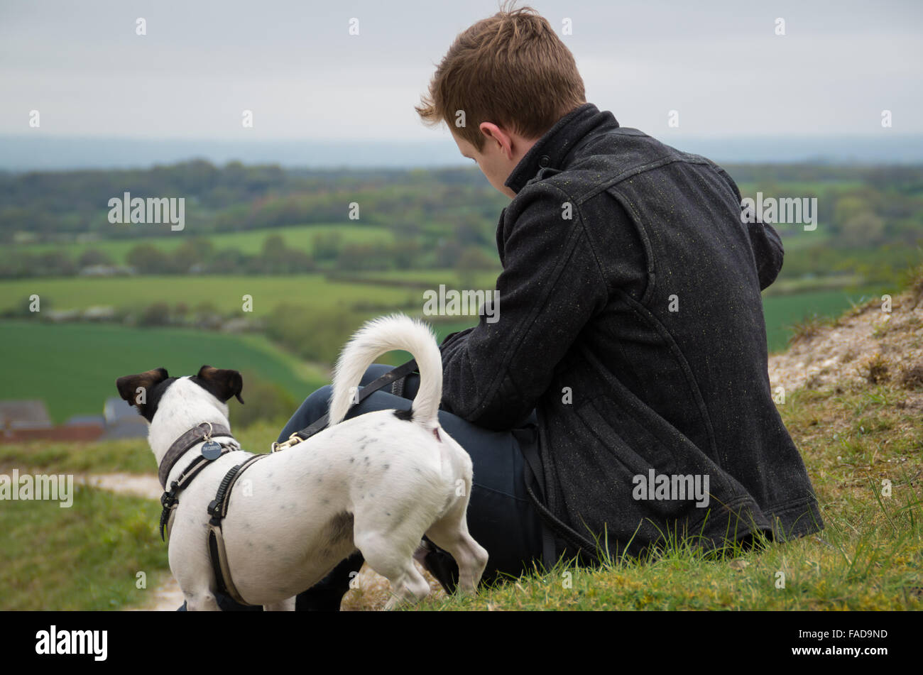 Male in late 20's with his Jack Russell Terrier sitting down overlooking the hills of the West Sussex countryside - Stock Image