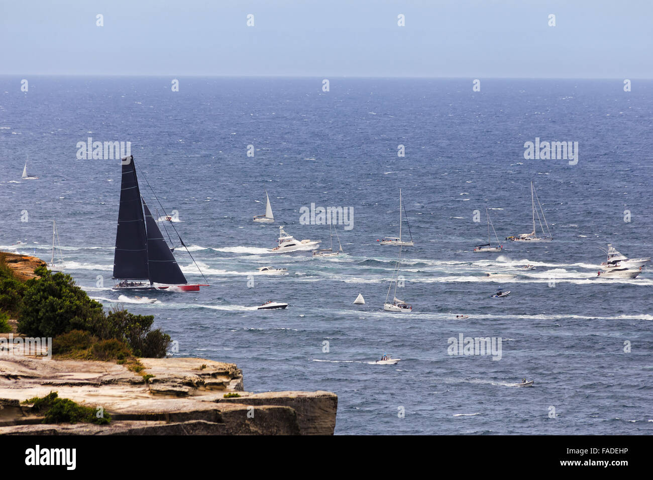 Leading super maxi yacht with black sail clearing from Sydney Habour Head surrounded by boats of spectators at Sydney - Stock Image