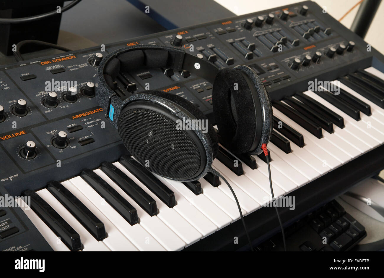 The synthesizer and headphones lay on it - Stock Image