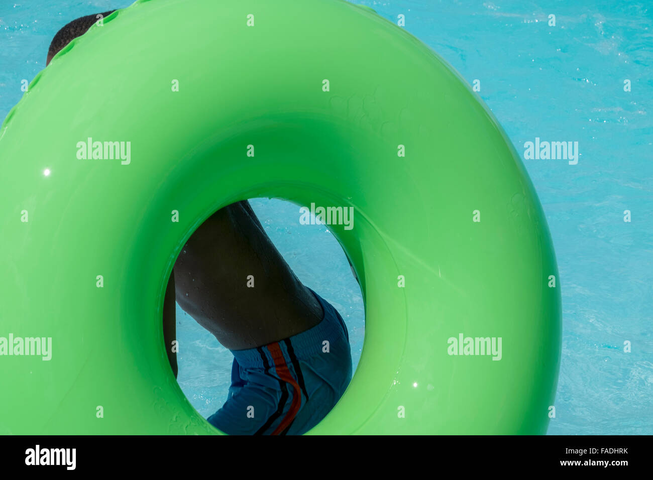 Young boy with a green inner tube at a swimming pool in the summer - Stock Image