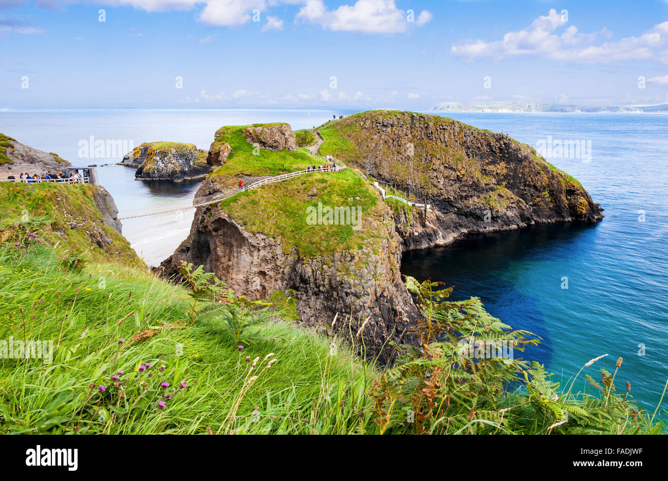 Tourist at the Carrick-a-Rede rope bridge on the Causeway Coast in Antrim County, Northern Ireland - Stock Image