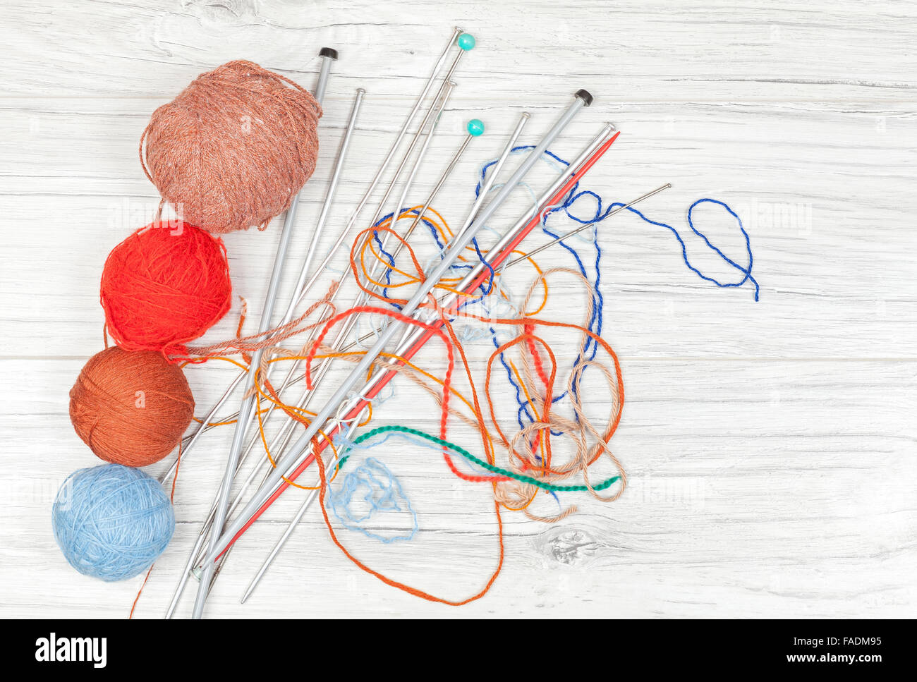 Tangled threads with yarn balls and needles on wooden board, concept background with space for text. - Stock Image