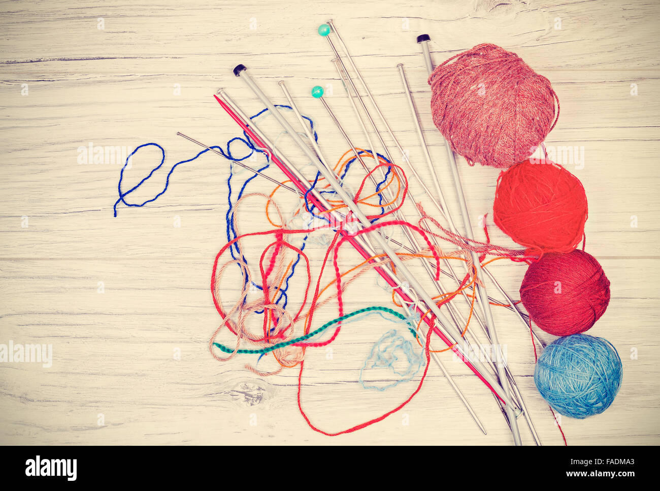 Retro toned tangled threads with yarn balls and needles on wooden board, concept background with space for text. - Stock Image