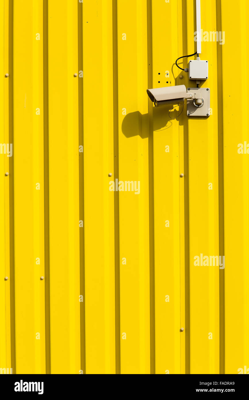 Security camera on a yellow wall - Stock Image