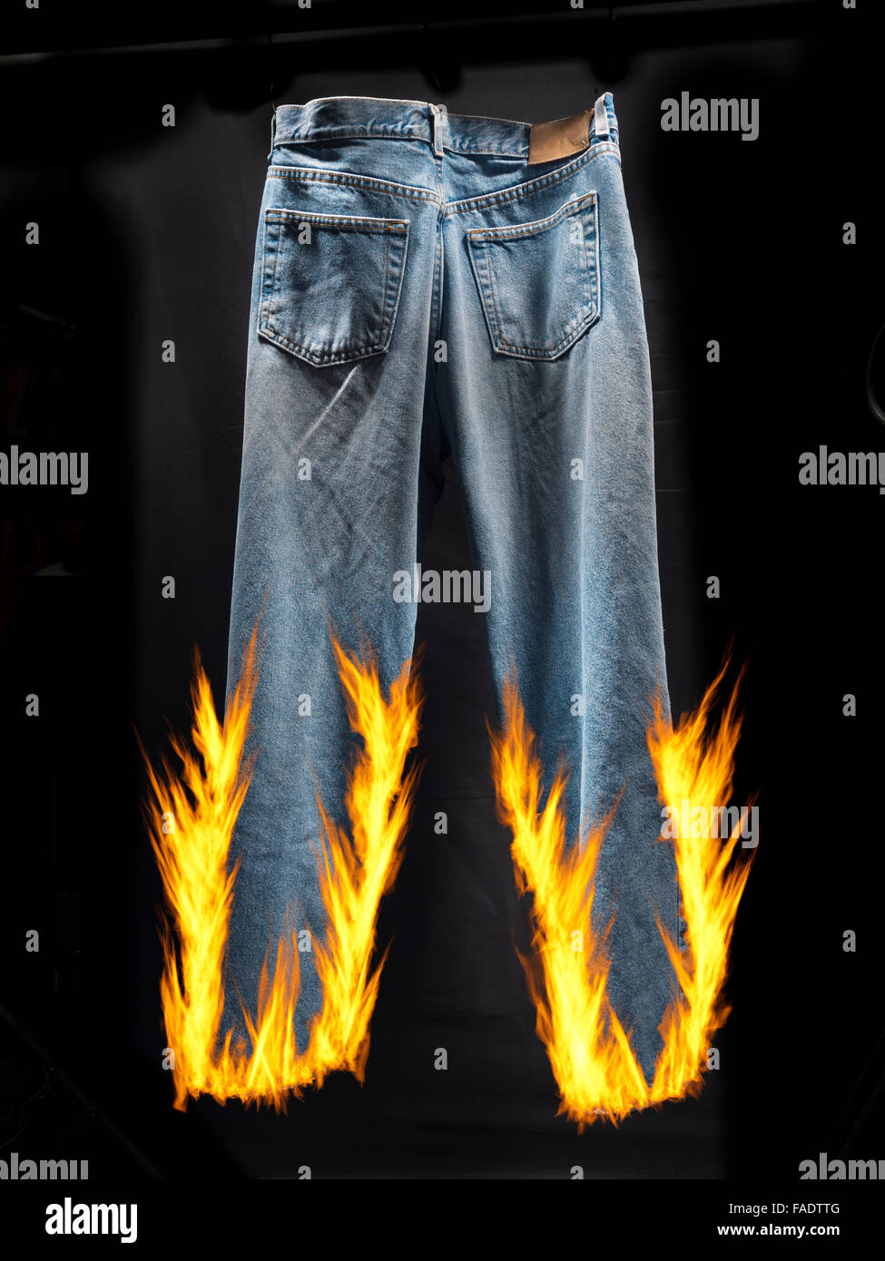 Blue jeans set on fire for idiom,liar,liar,pants on fire - Stock Image