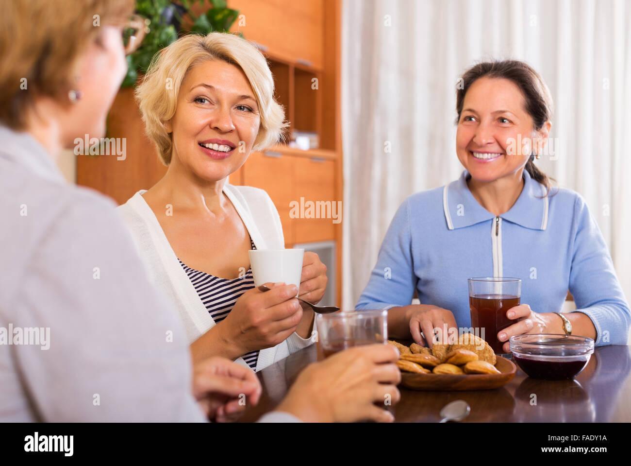 Happy mature women having coffee break at office. Focus on blonde woman