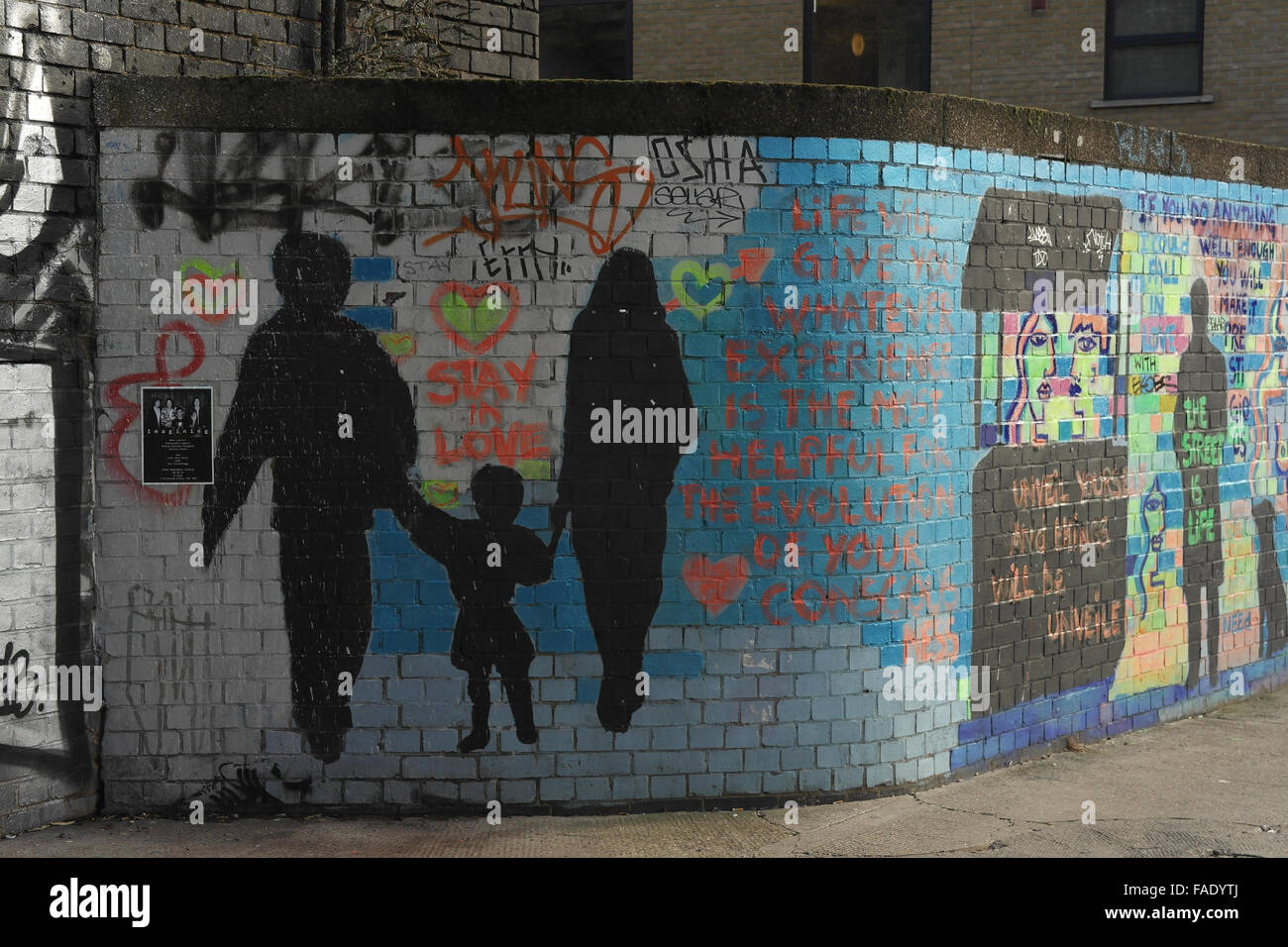 Multi-coloured brick wall with life captions, black stencils man woman holding arms child, Wheler Street, Shoreditch, - Stock Image