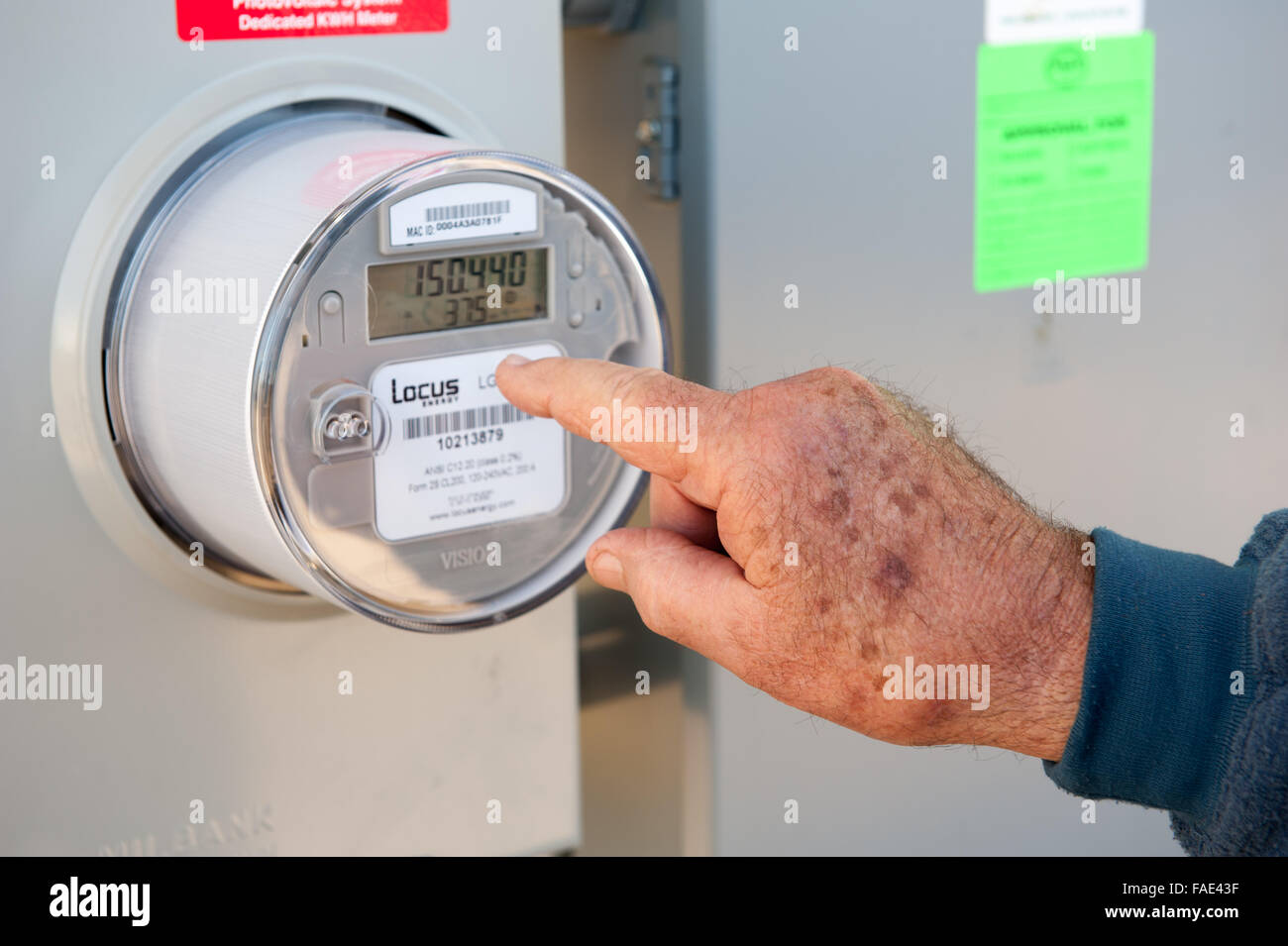 Man's hand pointing to an electric meter - Stock Image