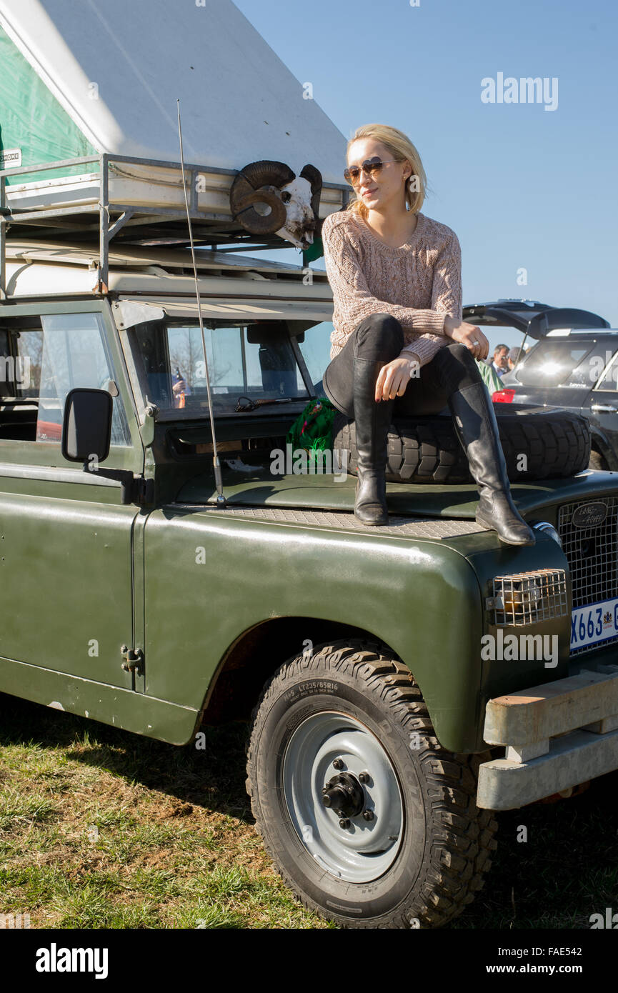 Woman sitting on top of a Land Rover - Stock Image