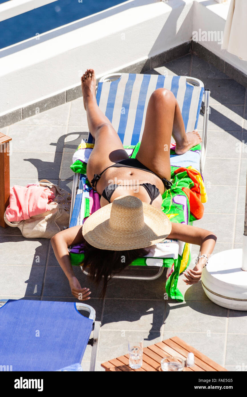 Santorini island. Tanned young Caucasian slim woman laying on sun lounger with black bikini on and straw hat over - Stock Image