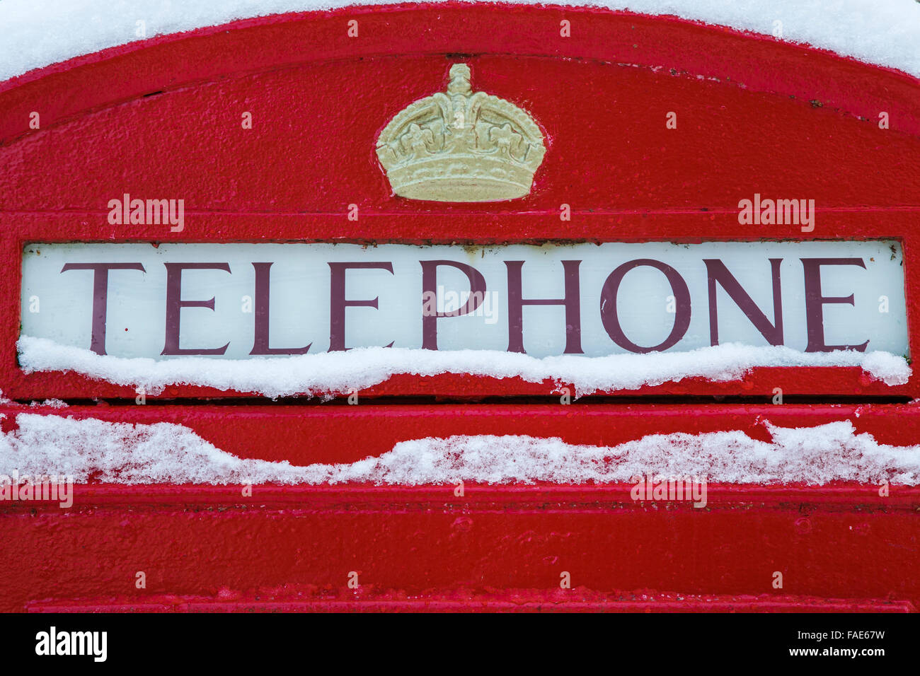 Old fashioned red telephone box in the snow, UK - Stock Image