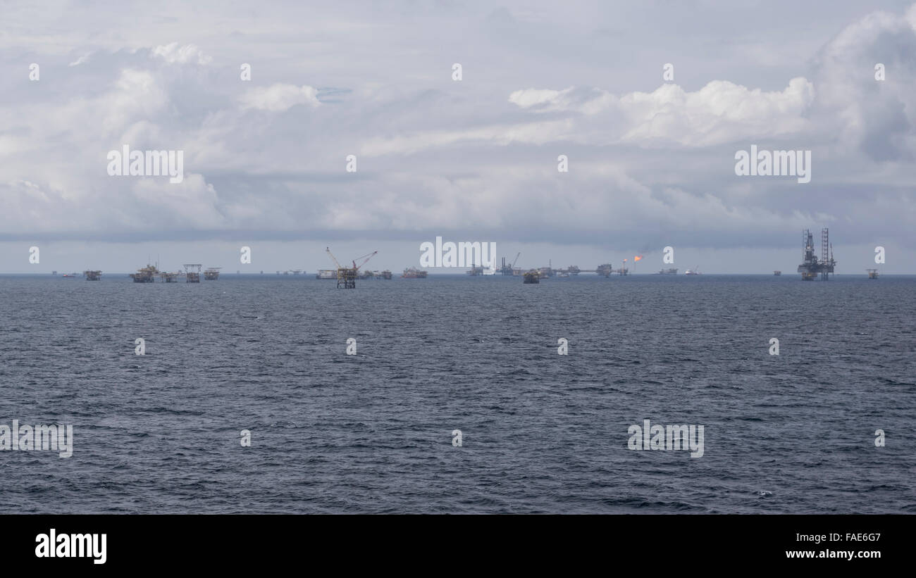 Many offshore oil rigs on the horizon off the coast of Brunei Darussalam, South China Sea. Cloudy sky. Stock Photo