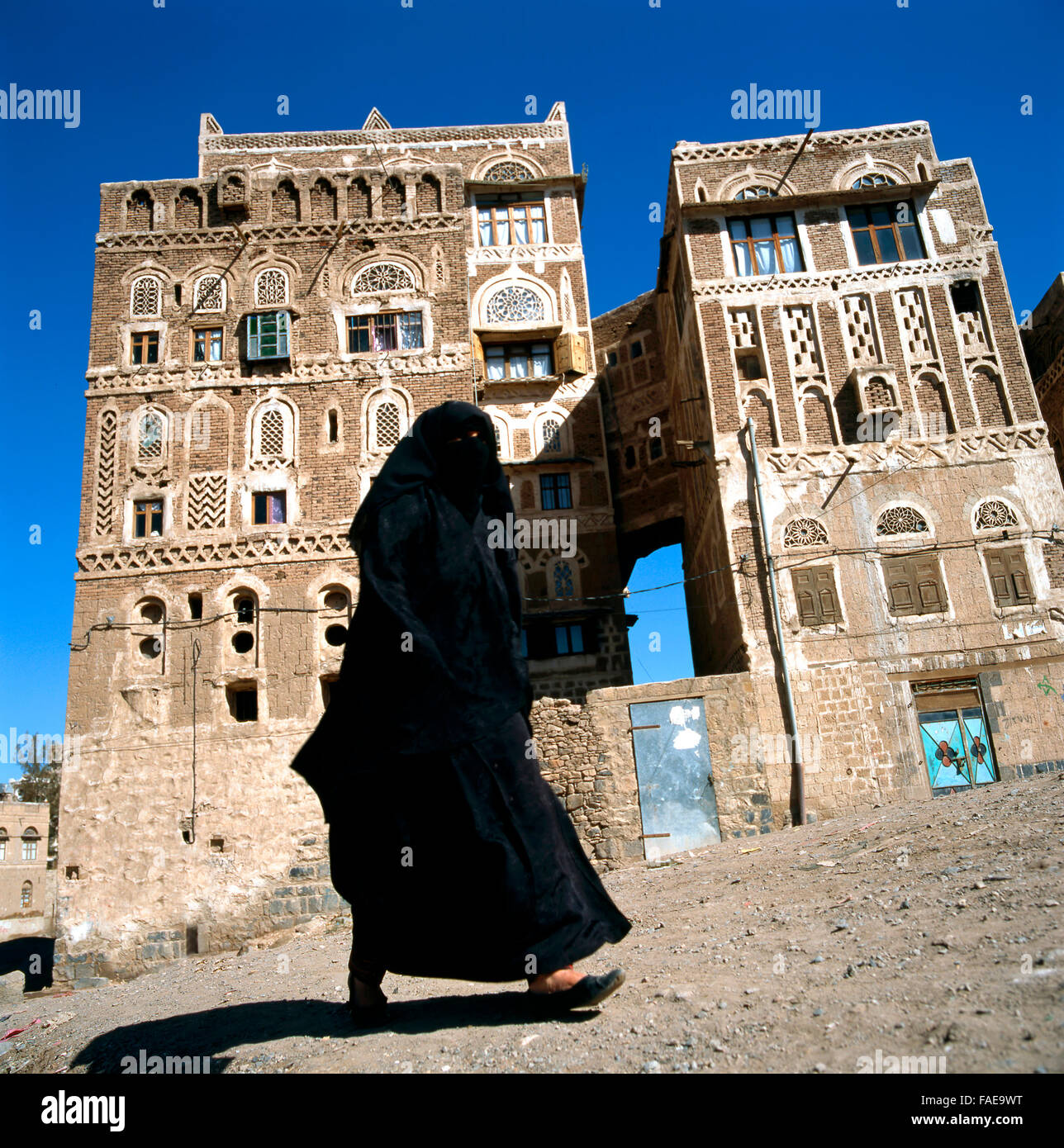 A veiled Muslim woman walks on a Sanaa street, Yemen.At background typical Yemen houses. - Stock Image