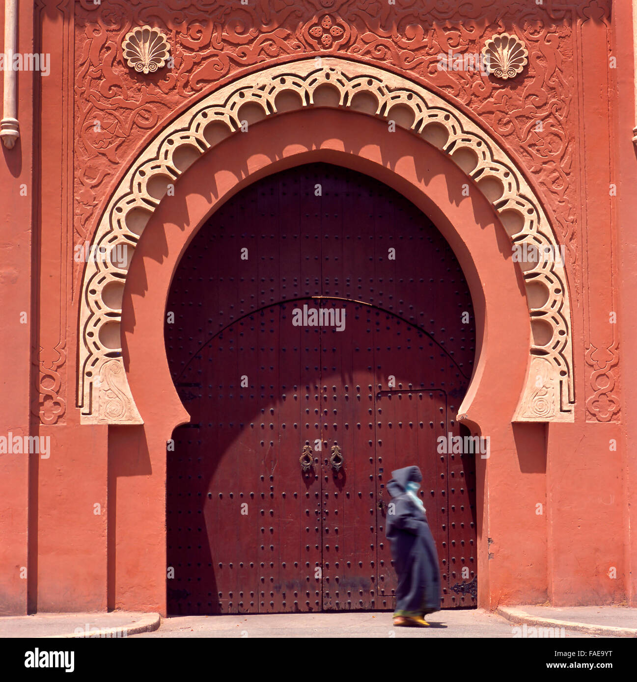 Marrakesh medina decorated gate.Lady is not recognizable because of total veil. Stock Photo