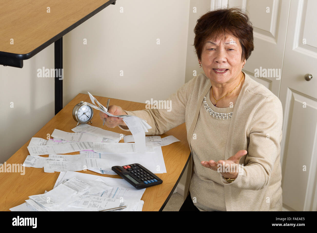 Senior woman expressing extreme anger while working on her financial bills. In debt concept. - Stock Image