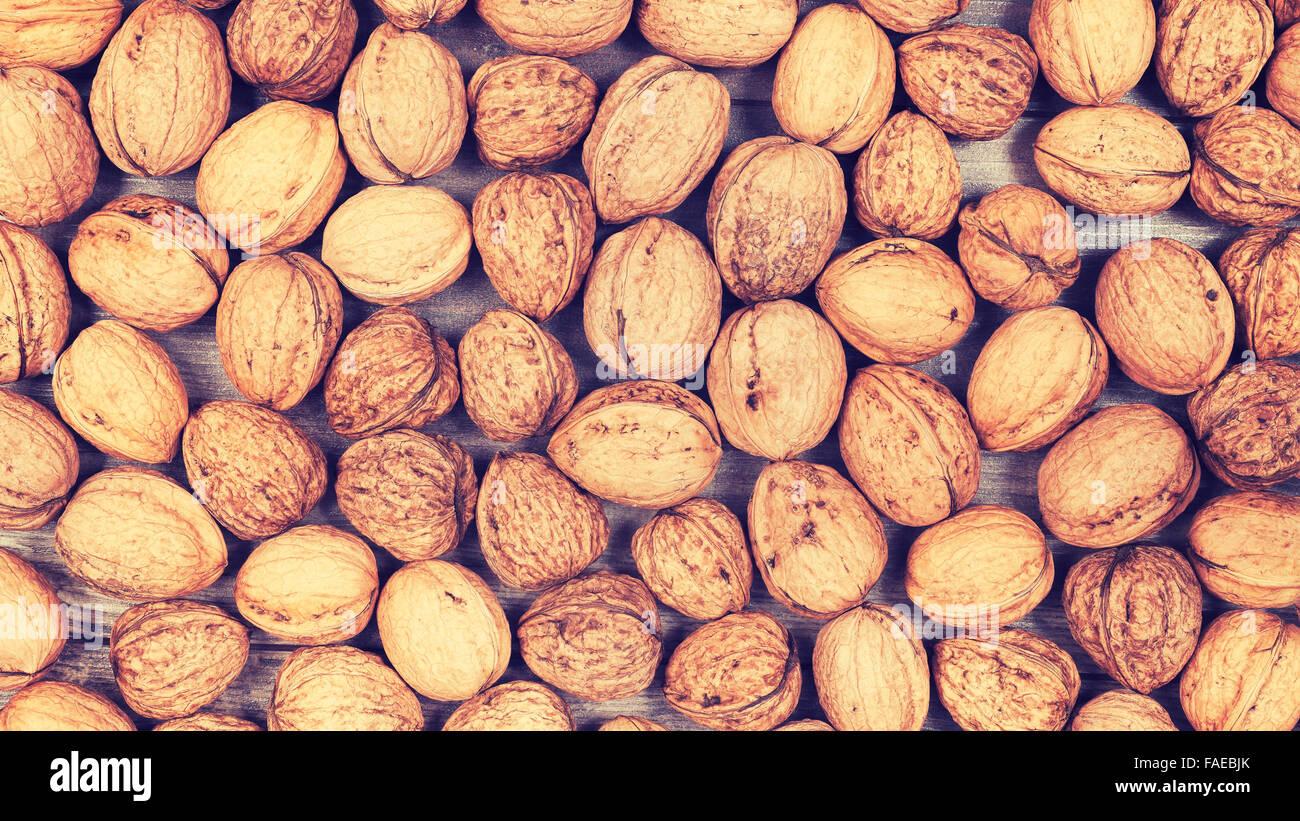 Vintage stylized background made of many walnuts. - Stock Image