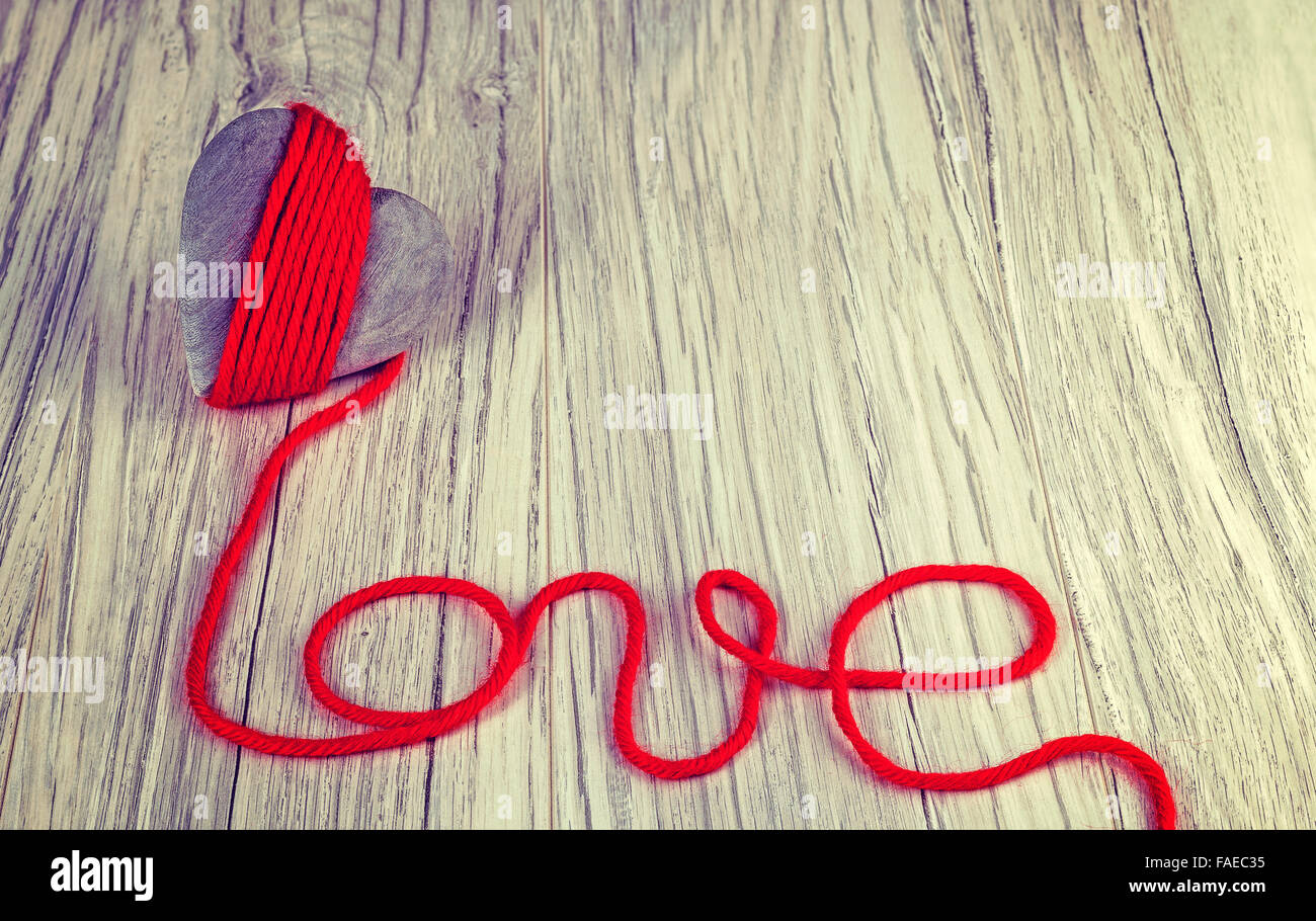 Vintage stylized wooden heart with red yarn love sign, space for text. - Stock Image