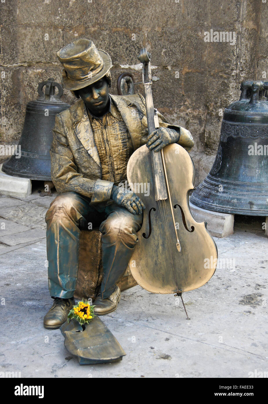 Street performer dressed as bronze statue with cello, outside church of San Francisco de Asis, Habana Vieja (Old - Stock Image
