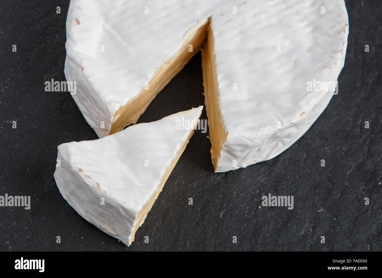 Segment of Brie cut from a whole English Brie cheese - Stock Image