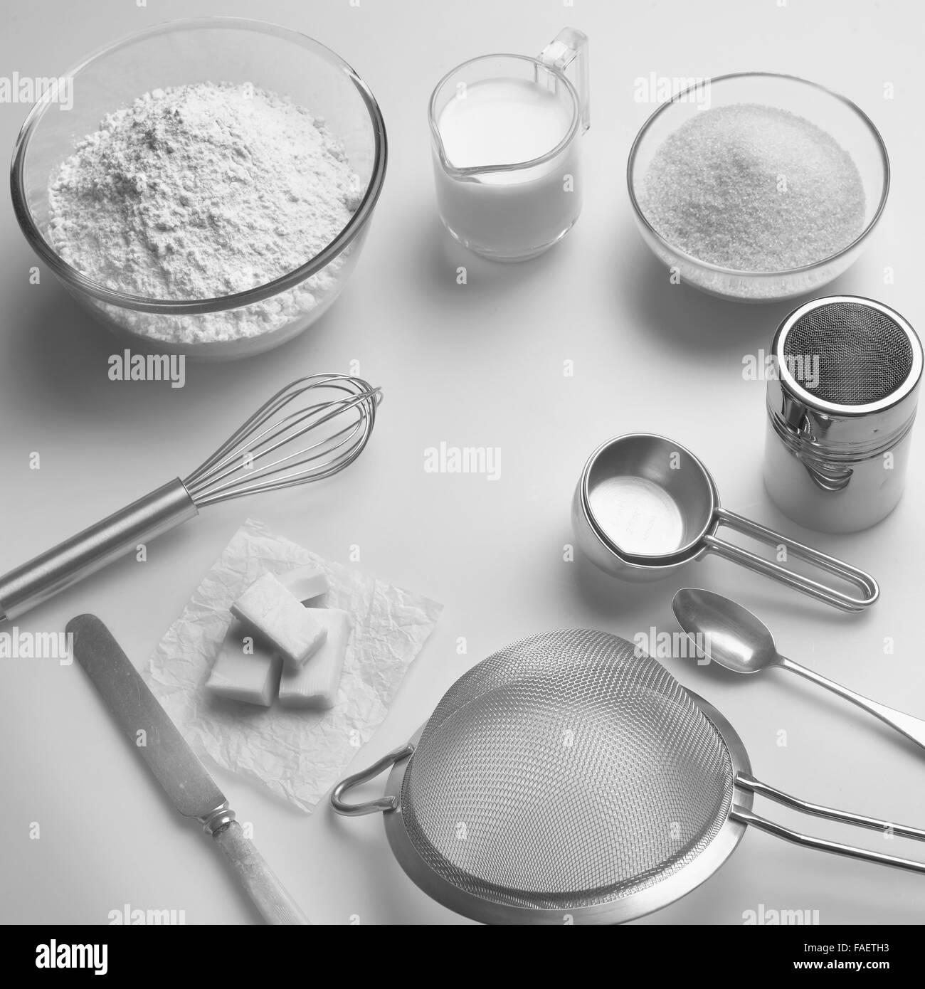 Black and white image of assorted kitchen utensils and raw food ingredients for home baking. - Stock Image