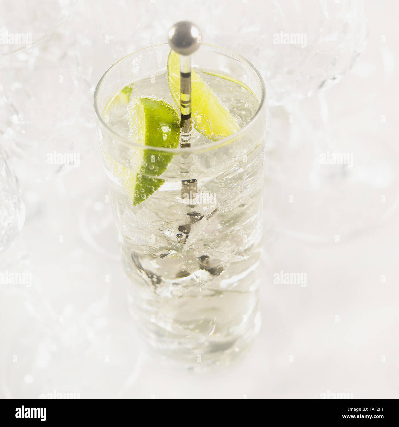 Glass of gin and tonic with ice, fresh sliced lime and drink stirrer. Stock Photo