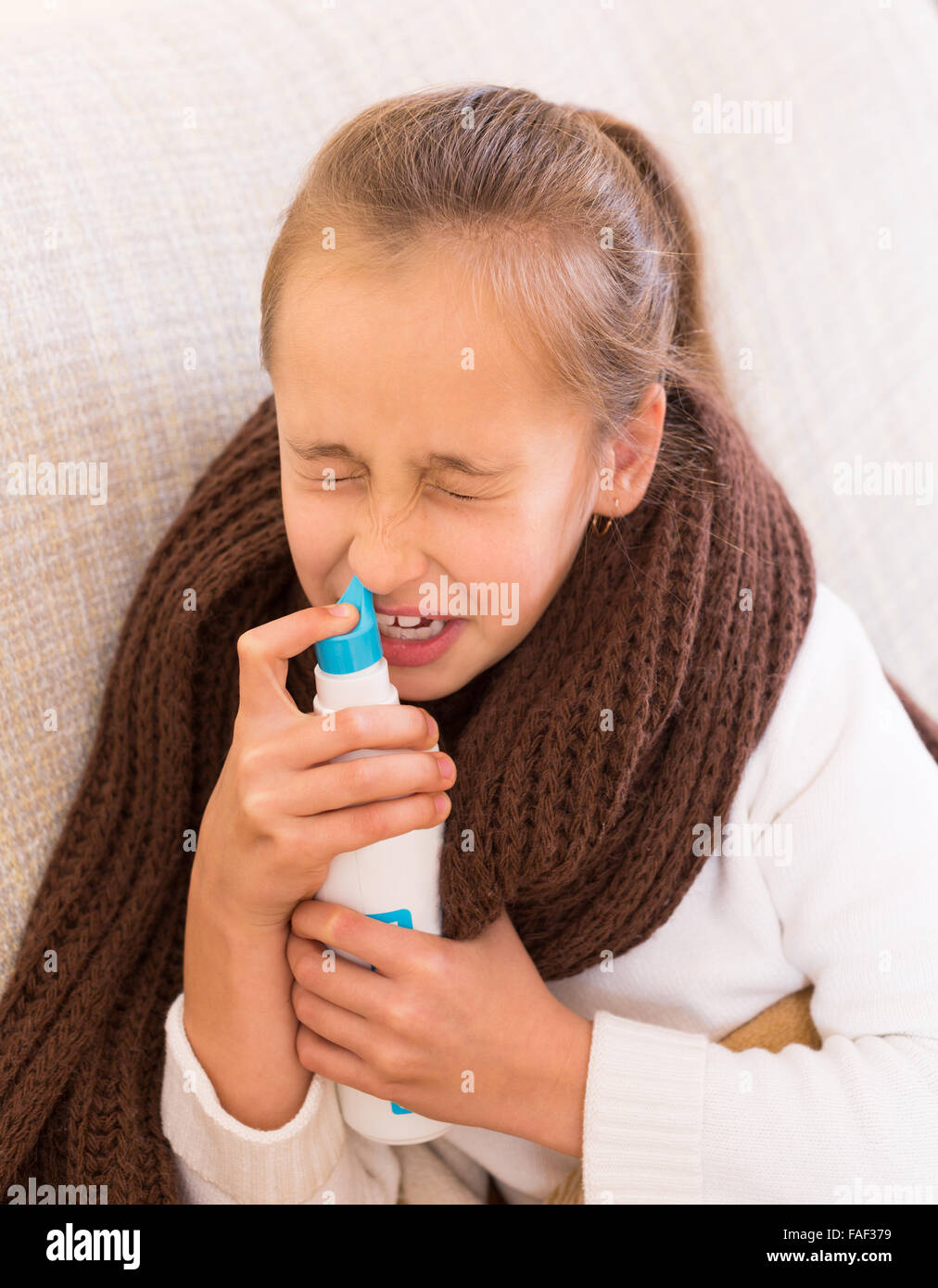Sick child sitting on couch with nasal sprayer for rhinitis - Stock Image