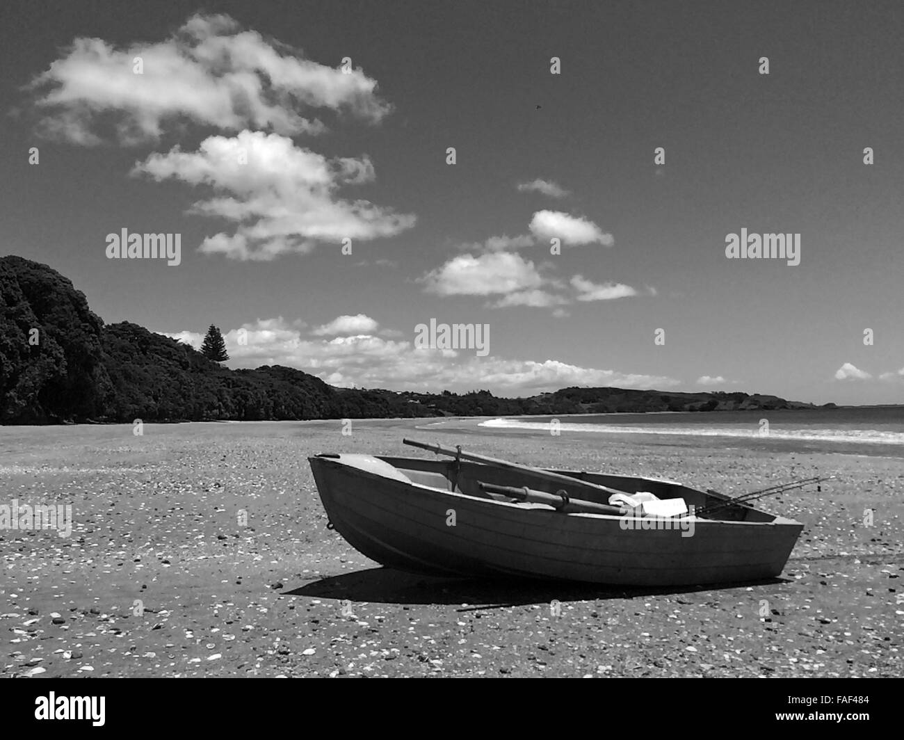 Fishing boat on a sandy beach during summer holiday vacation.(BW) - Stock Image