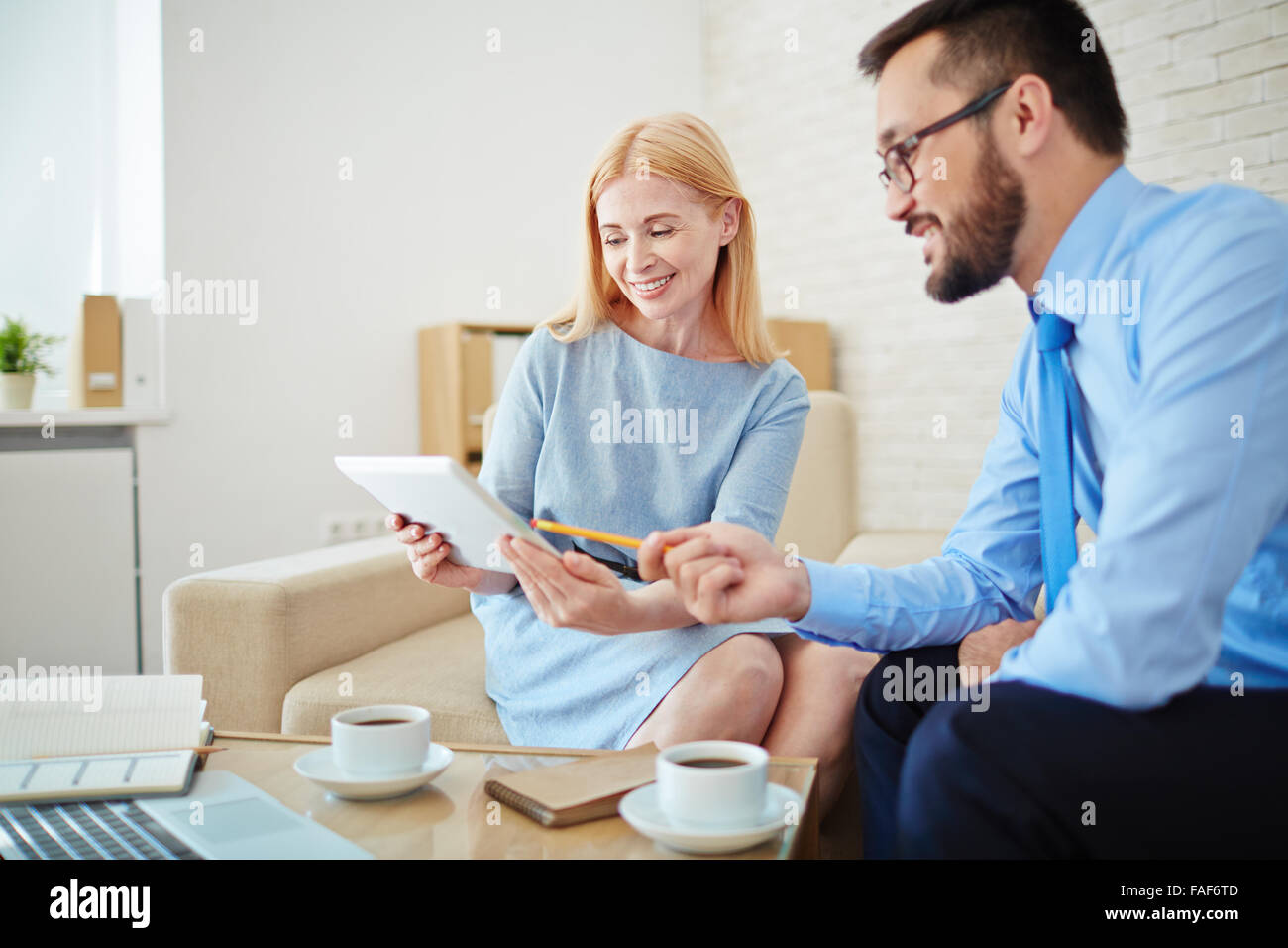 Business people working together and using touchpad at office - Stock Image