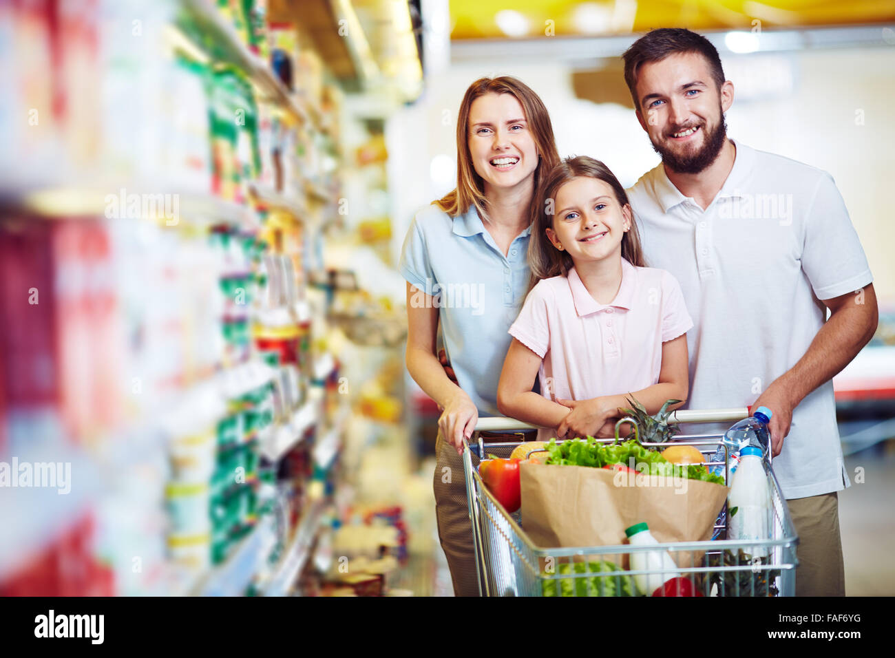 Family with chopping cart during shopping at vegetable supermarket - Stock Image