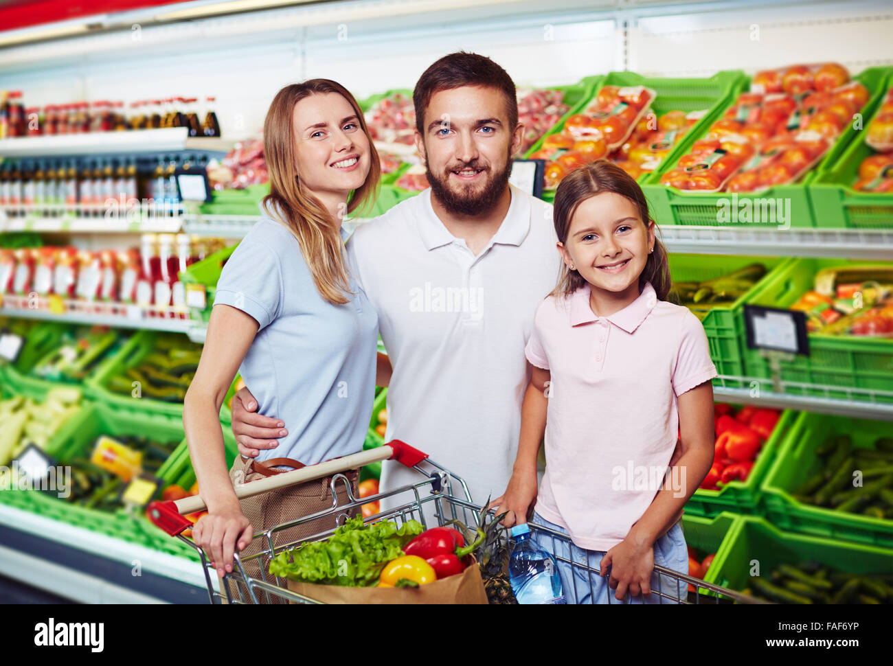 Portrait of happy family shopping for groceries in supermarket - Stock Image
