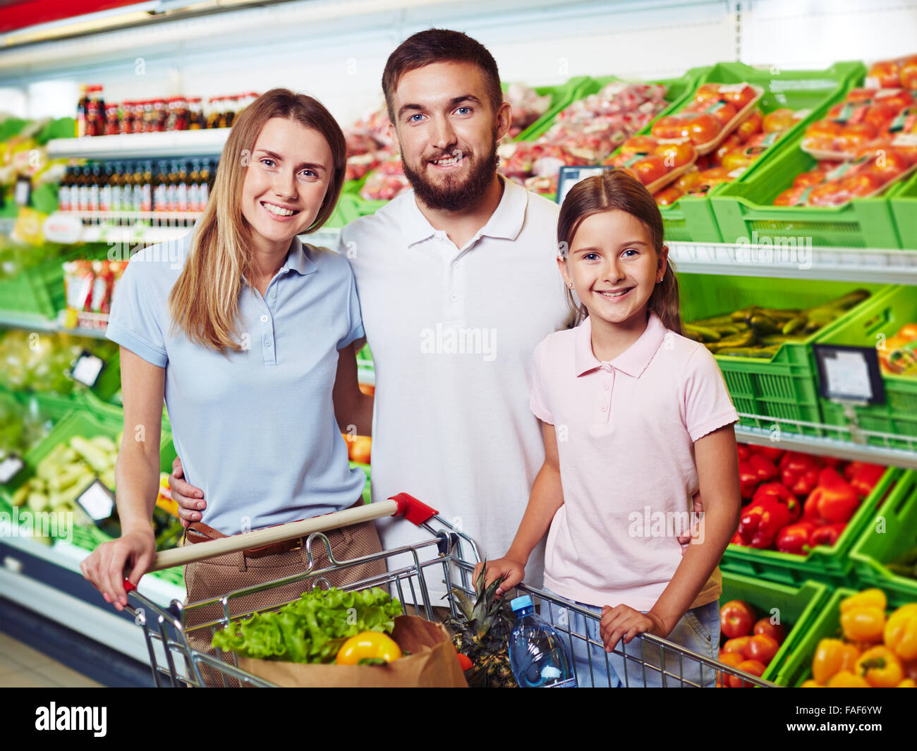 Family of three shopping in grocery supermarket - Stock Image