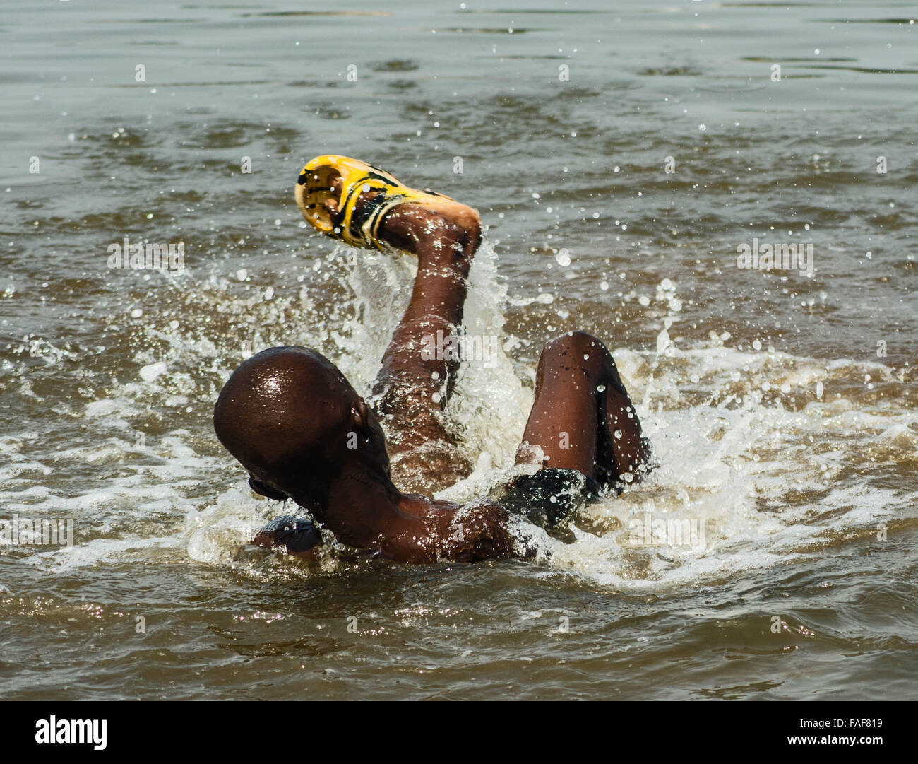 Boy playing in dirty water in Freetown, Sierra Leone Stock Photo
