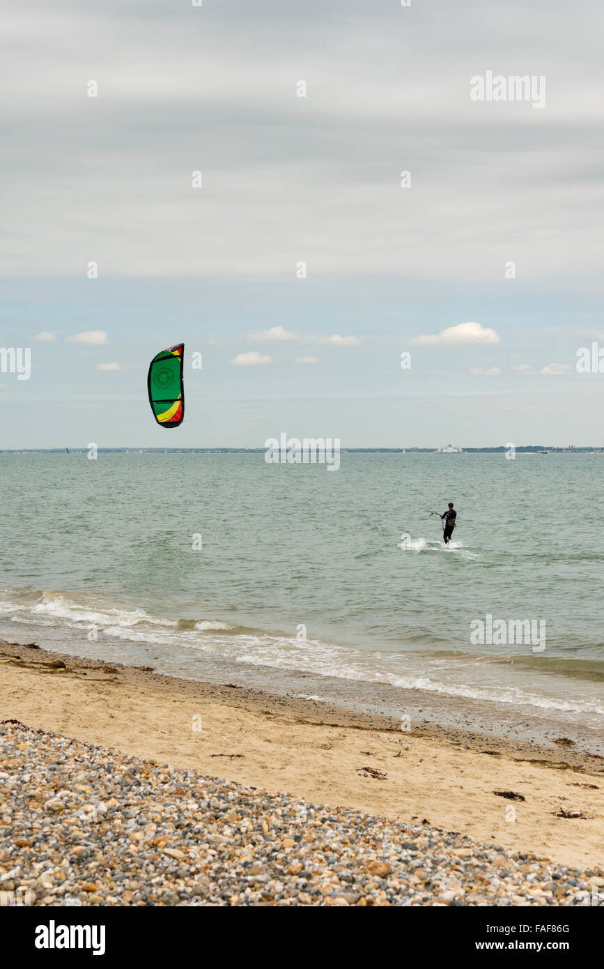 A Kite surfer kitesurfing on the sea on the Isle of Wight UK on an overcast day - Stock Image