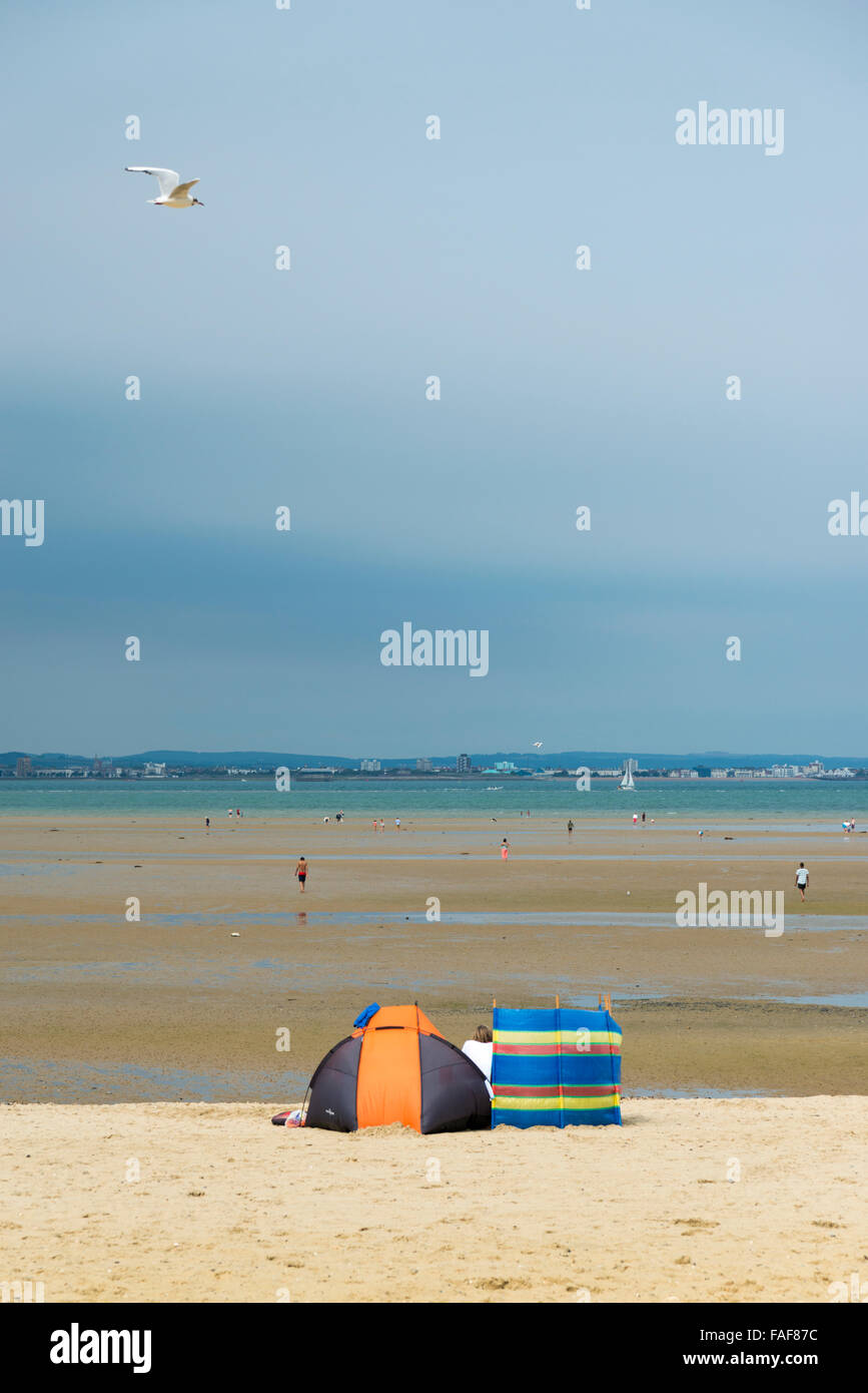 The beach at Ryde Isle of Wight at low tide with large stretch of sand and beach shelters in summer - Stock Image