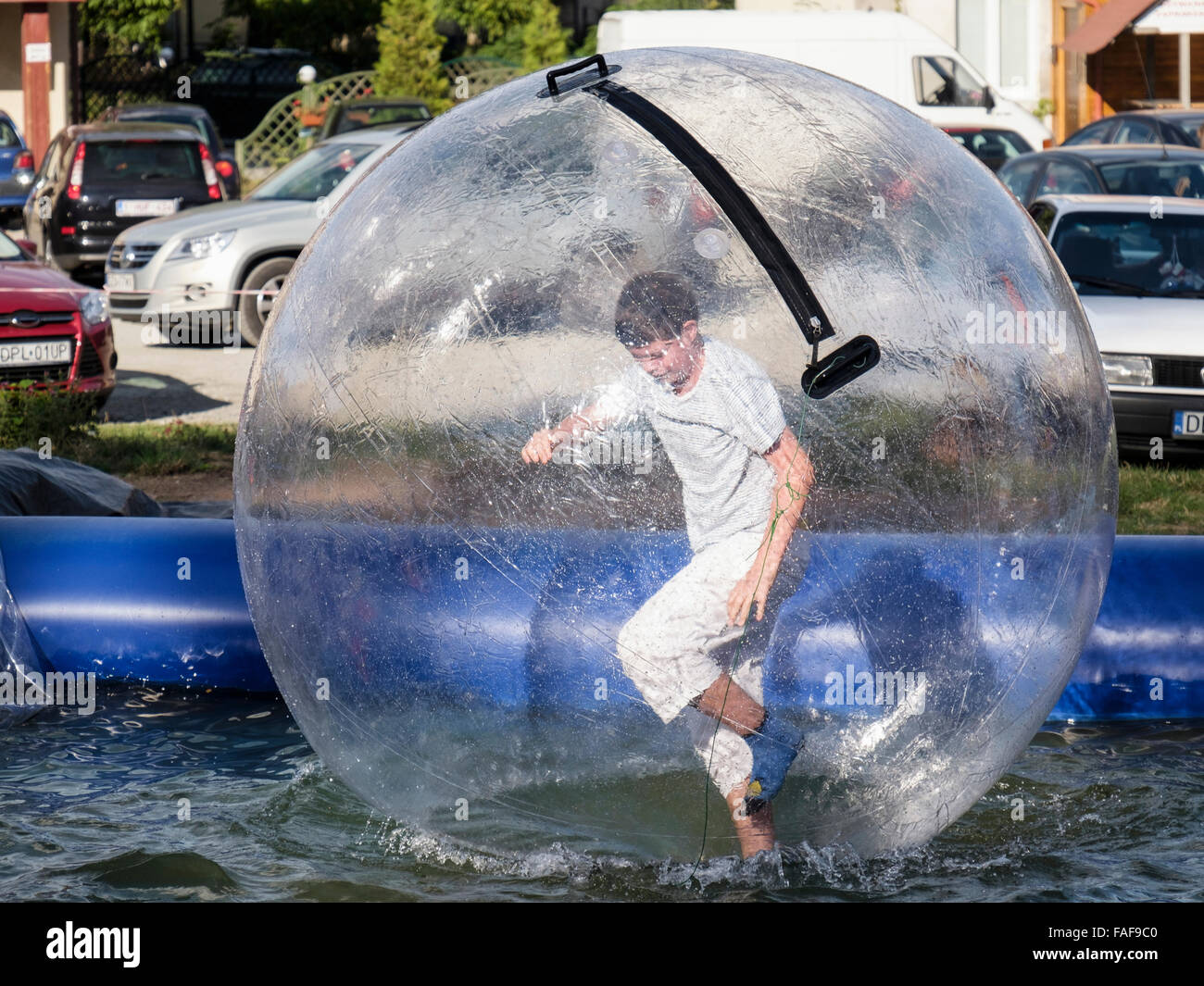 Boy standing up running in an inflatable ball bubble zorbing on a pool of water. Polanica-Zdroj, Klodzko, Poland, Stock Photo