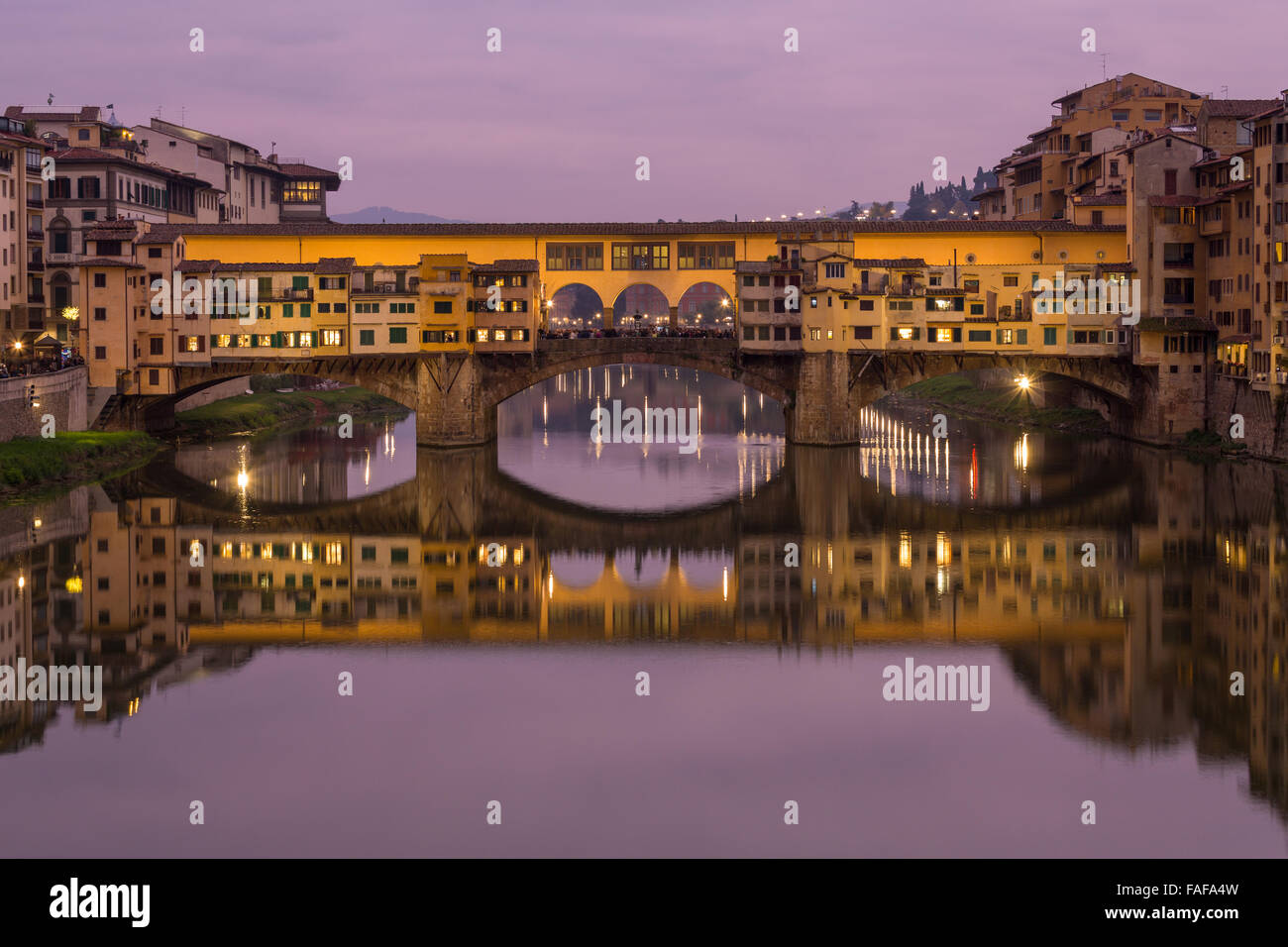 Ponte Vecchio over the Arno with symmetrical reflection in water, dusk, Florence, Tuscany, Italy - Stock Image