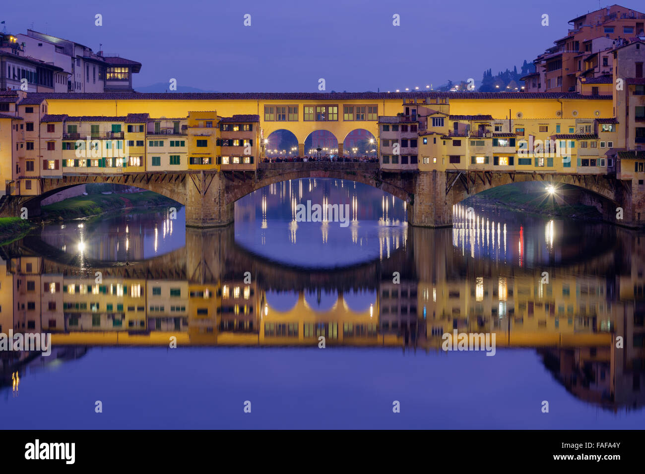 Ponte Vecchio over the Arno with symmetrical reflection in water, Blue Hour, Florence, Tuscany, Italy - Stock Image