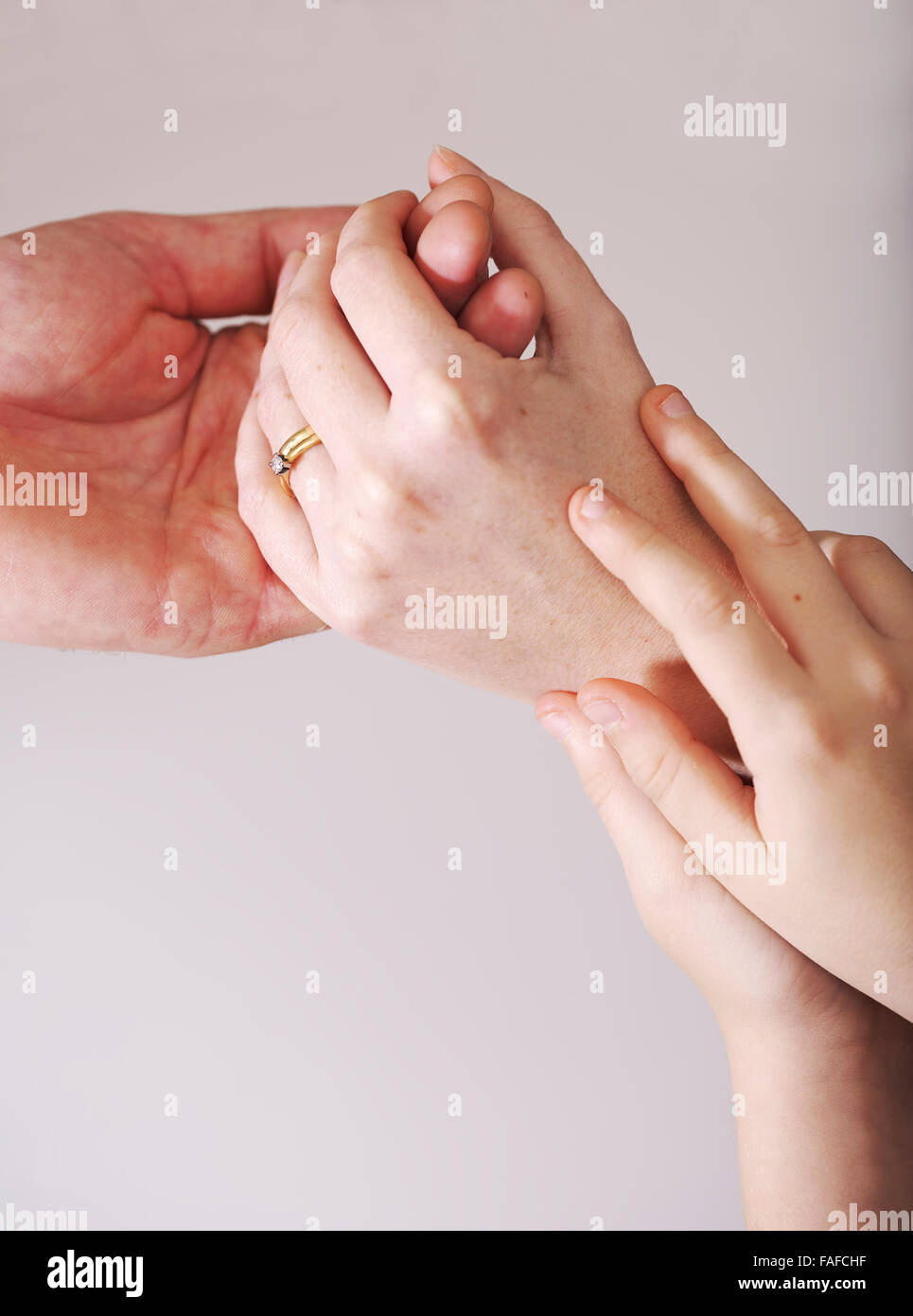 Child holds the hands of mother and father during a fragmented and strained relationship Stock Photo